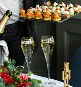 Two glasses of champagne and a tray of canapés