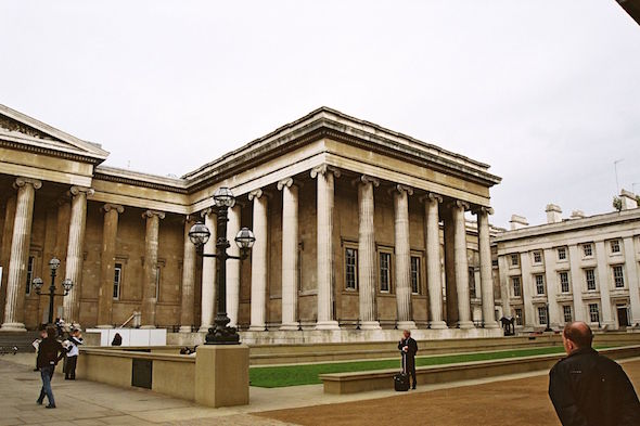 landscape picture of the exterior of the British museum front entrance with pillars during daytime including public