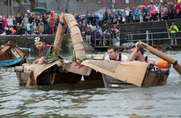 People taking part in cardboard boat racing as part of the Bristol Harbour Festival