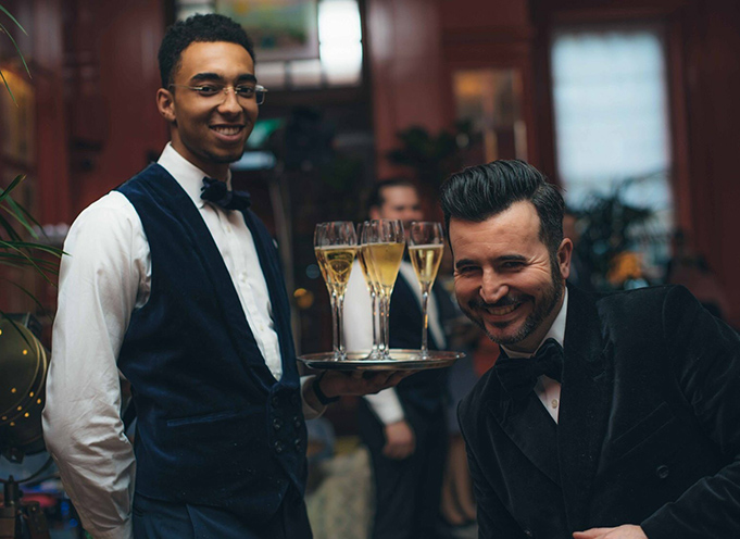 Bar man holding tray of drink. Host smiling