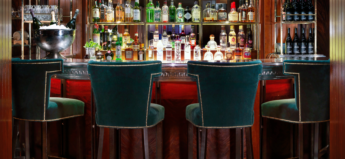 The bar at the Bloomsbury Club with green chairs and image of the bar with drinks