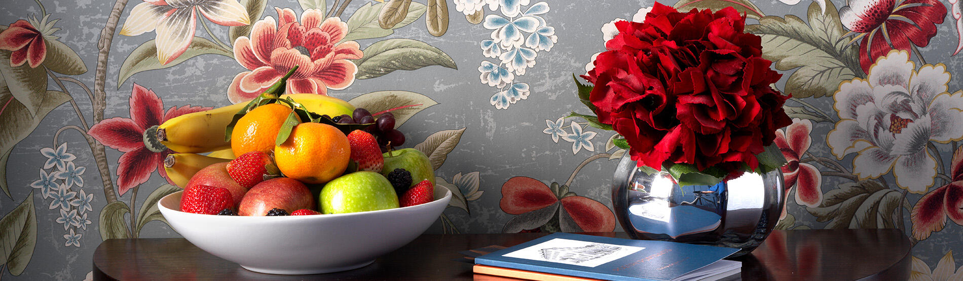 A vase of red flowers and bowl of oranges, bananas, apples and strawberries on a wood table