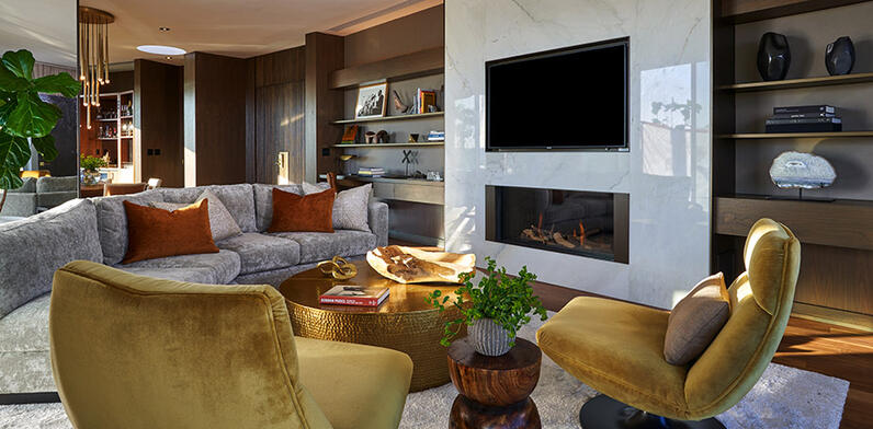 Living room with sofa and armchairs in front of fire and TV
