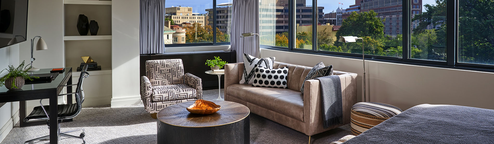 Suite living room with large windows and view of city