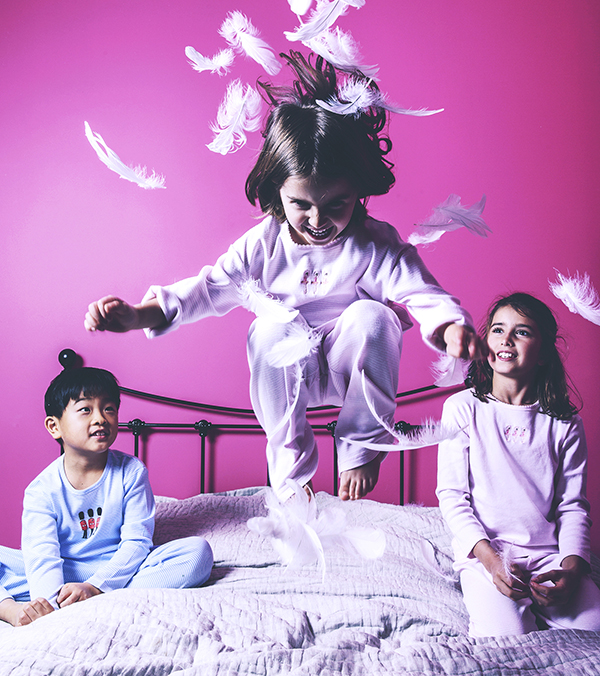 Children jumping on a bed