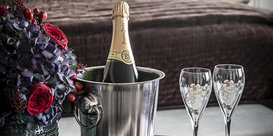 Bottle of Perrier Jouet champagne in an ice bucket with two glasses