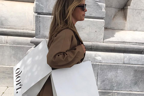 Woman wearing sunglasses with Olori boutique shopping bag