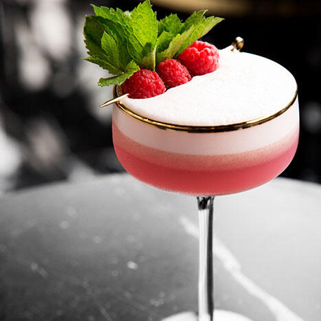 Pink cocktail with raspberries and mint on top