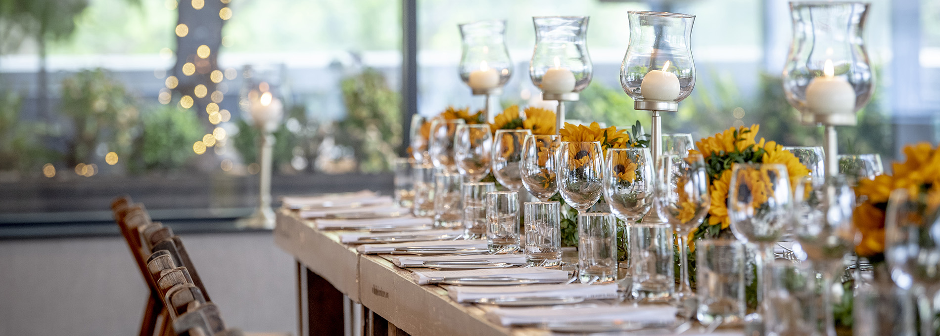 Long table set for dinner with sunflowers and candles