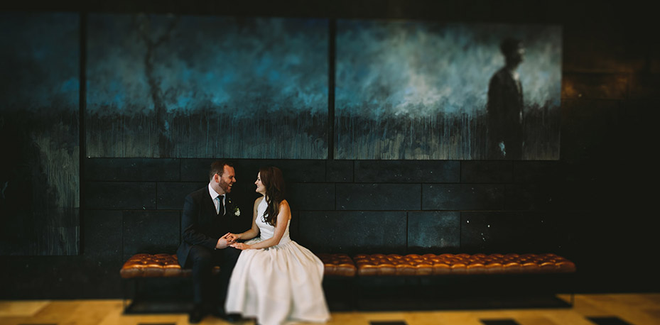 Ian and Rebecca sit and hold hands under hotel lobby artwork