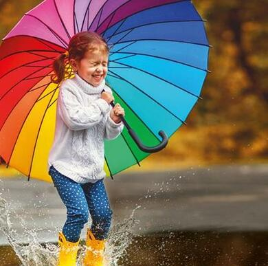 girl with umbrella jumping in puddle